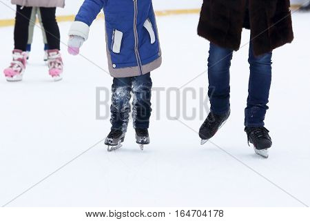 the child and the man skating on the ice rink.
