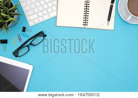 Office table desk with computer tablet pen coffee cup flower eye glasses supplies and white blank note pad on blue background Top view and copy space for text