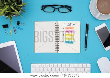 Smart goal setting on notebook with office supplies computer eye glasses and coffee cup over blue desk background Business success concept