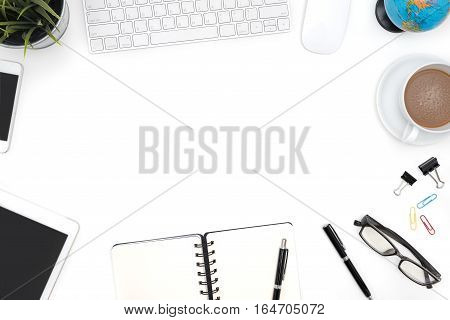 Frame of white office desk table background with computer supplies notebook pen pencil tablet phone flower globe eye glasses and coffee cup Top view with copy space