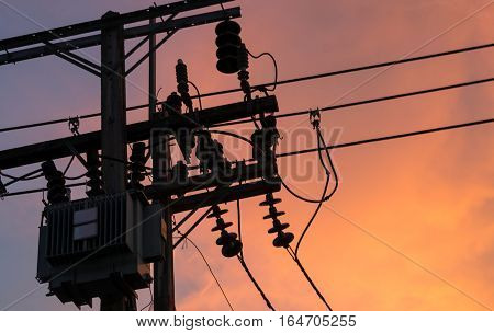 Sunset and silhouette of electrical transformer on pole