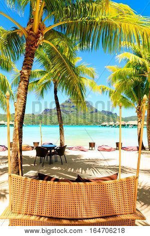 Palm trees and cozy chairs on tropical beach in Bora Bora French Polynesia