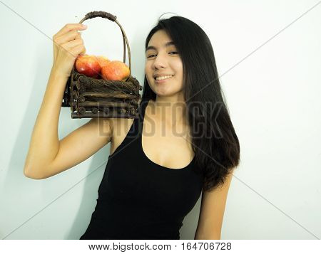 Asian woman holding red apple in wooden basket on white background have a big smile