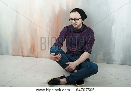 Studio Portrait Of A Young Man Hipster. Guy With Beard Wearing Glasses, Hat And A Plaid Shirt, Sat O