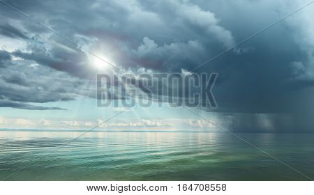 Dramatic sky with large clouds above the lake against black mountains. Lake Baikal.