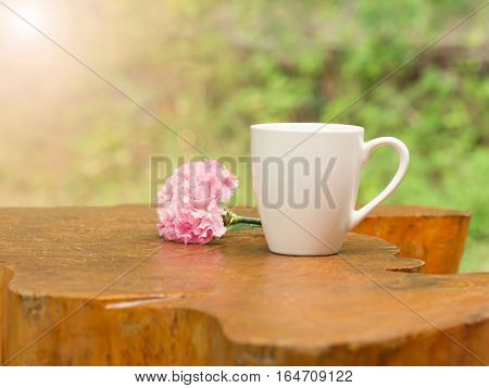 White cup of hot coffee with pink flower on wood table in natural green background in morning.