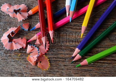 A top view image of several brightly coloured pencil crayons on a rough wooden surface.