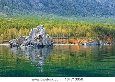 Colorful forest with reflection in water and rock