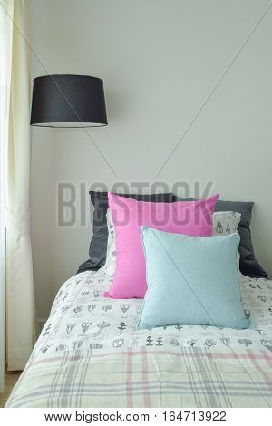 Pink And Light Blue Pillow On Single Bed With Black Shade Standing Lamp