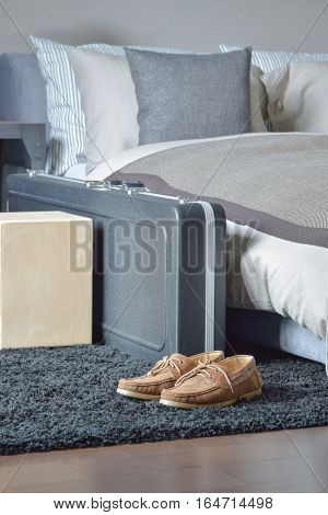 Brown Leather Shoe And Luggage  On Black Rug Next To Bed In Modern Style Bedroom
