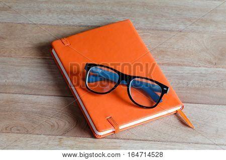 close orange notebook on wood background withe glasses