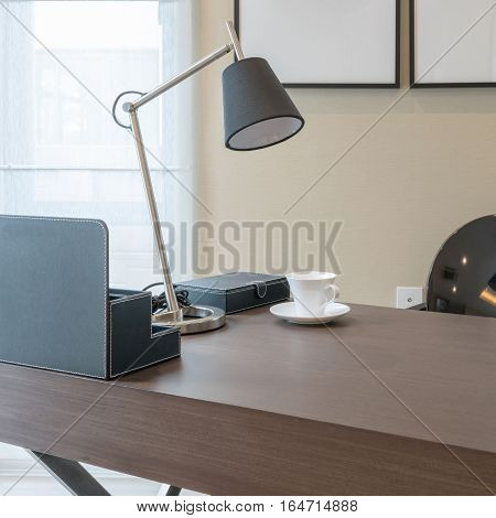 Wooden Table With Reading Lamp And Tea Cup In Modern Working Room Interior