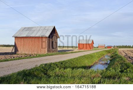 Red wooden barns along a gravel road. Farmland in the surrounding. Dike, water this side.