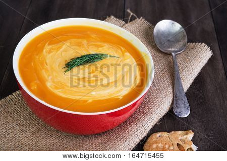 Pumpkin and sweet potatoes soup with sour cream dill and pumpkin bread on dark wooden table