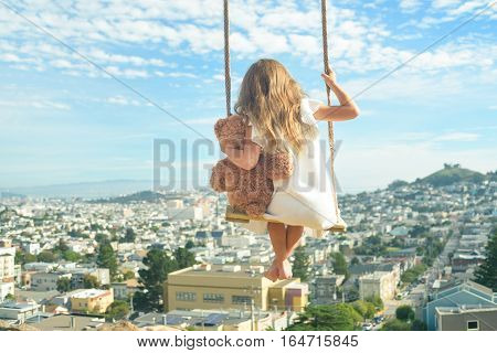 Barefoot girl in white dress hugging teddy bear flying on vintage swings high above city view from behind