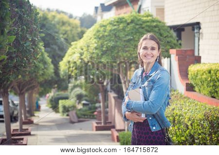 Young attractive woman with books standing in sunny street. She looks successful she is smiling happily she has a whole future ahead of her.