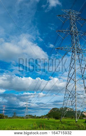 High voltage electricity pylon on the confield have moutain and sky on blackground