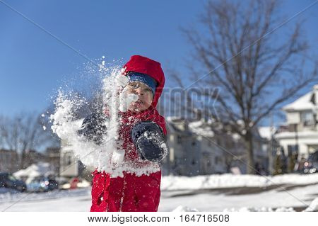boy having fun in the snow. play snowballs outdoors. joyful boy throws a snowball at the opponent and get a snowball in the face