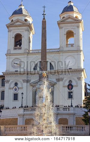 unusual Christmas tree, obelisk and church Trinita dei Monti on top of the Spanish steps in Rome, Italy