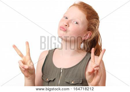 Portrait of a teenage girl showing victory sign on white background