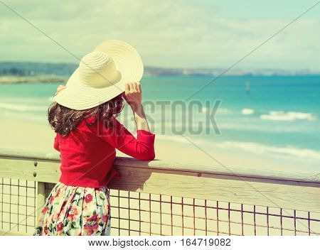 Beautiful woman in red standing and looking to the sea. Toned in retro style