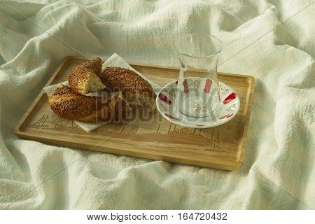 Bagel and empty cup for turkish tea on the wood tray with Istanbul picture on the bedcover breakfast in bed