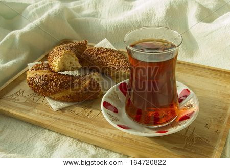 Bagel and cup of turkish tea on the wood tray with Istanbul picture on the bedcover top down view