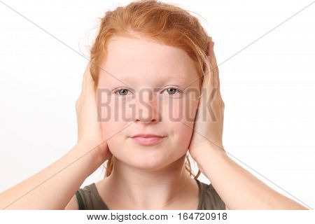 Portrait of a teenage girl covering ears with hands on white background