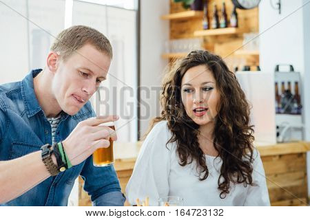 Blond man drinking craft beer with froth on mouth.Brunette looking at glass