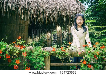 outdoor portrait of girl standing on atched bamboo thai traditional house in park vintage style