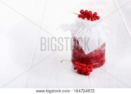 Schisandra chinensis or five-flavor berry jam on white. Five-flavor berries with sugar in a glass jar fresh red berries spread layers interspersed with sugar. Copy space.