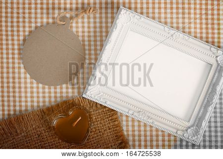 Top view of empty white photo frame and paper tag next heart sign from candle in glass over the fabric clipping path ready to put photographs.