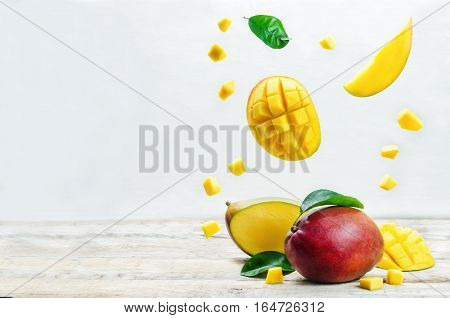 mango with flying slices on a white wood background