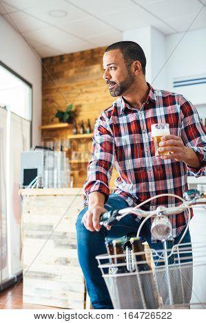 Bearded man on bike holding glass of light craft beer