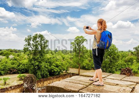 Tourist Taking Picture From Top Of Temple In Angkor, Cambodia