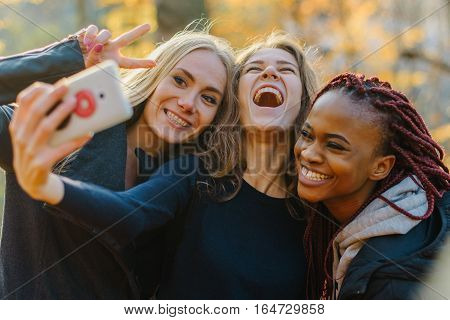 Three Pretty woman making selfie in autumn park. Cute girls with different colored skin. Female making funny faces and smiling at camera