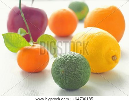 Selection of fresh fruit arranged in the heart shape on white wooden table. Selective focus on the front.