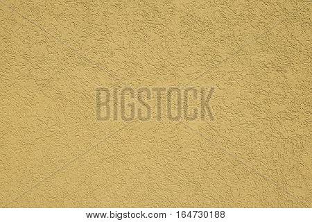 Yellow classical facade plaster on house, medium coarse texture of handmade plaster