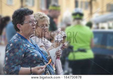 Garda Itali - May 182015: Two corpulent ladies talk holding huge portions of the ice cream corresponding to their proportions in hand.