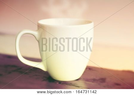 closeup of white steamy cup on red wooden table