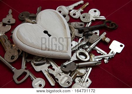 White wooden heart shape with a keyhole on a lot of keys but no one fits and can unlock it concept of the one true love valentine's or mother's day red fabric background