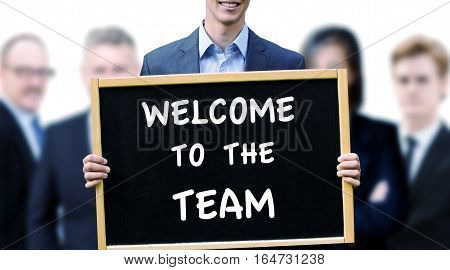 young businessman holding a sign with the words Welcome To The Team and group of people behind him