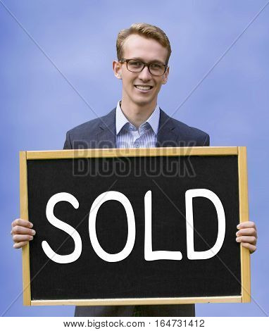 young businessman holding sign with the word Sold