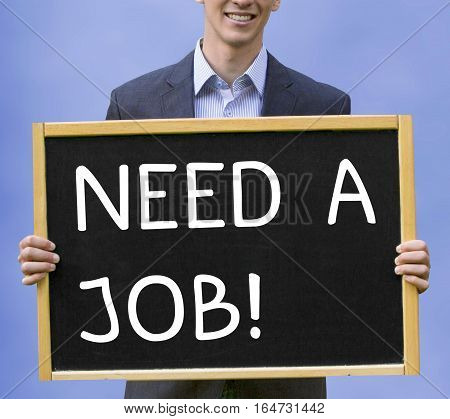 young businessman holding chalkboard with the words Need A Job