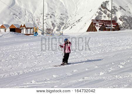 Little Skier At Ski Resort In Sun Winter Day