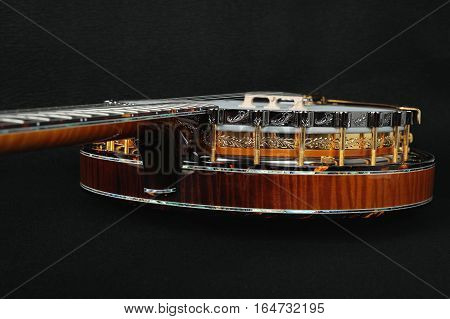 Mahogany banjo luxury gold inlaid with mother of pearl on a black background.