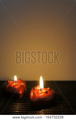 Two candles in the shape of hearts on a rich brown background