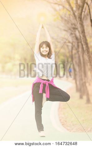 sweet dreamy and de-focused Attractive woman practices standing in Vrksasana Posture at nature garden Relax and active lifestyle concept soft focus in vintage tone
