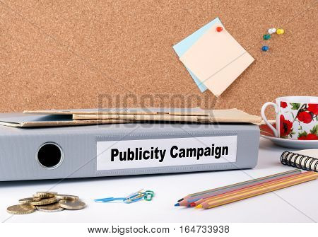 Publicity Campaign. Folder on office desk. Money, Coffee Mug and colored pencils.
