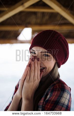 laughing young woman in burgundy hat covers face with her hands